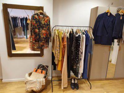Kläder som hänger på en klädställning. En brun spegel med en blus som hänger i en galge. En korg på golvet.