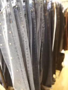 Flera par ljusa jeans som hänger på en klädställning.