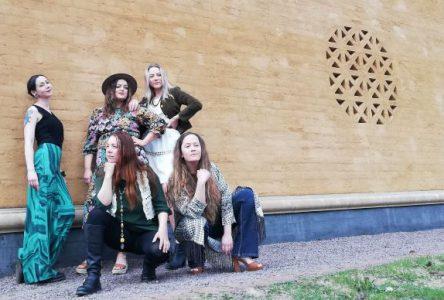 Fem kvinnor visar upp kläder som kan hyras hos Rekoroben. De står och sitter på hur framför en vacker vägg i sten vid Värmlands museum.