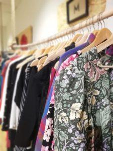 Blandade kläder som hänger på en klädställning. Det närmaste plagget är en mönstrad klänning med blommor i grönt, gult och rosa.
