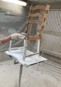 En stol i trä, som lackeras vit.