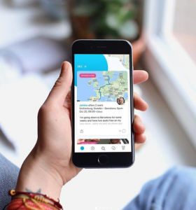 En hand som håller i en mobiltelefon som visar upp ett erbjudande om en samåkning från Göteborg till Barcelona