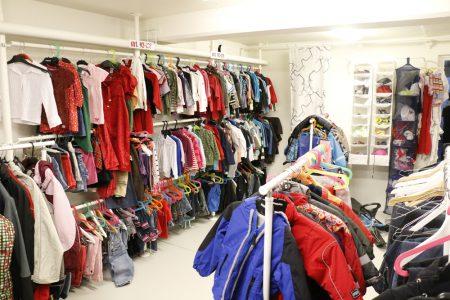 Ett rumt fyllt av klädhängare med en mängd barnkläder i olika färger.