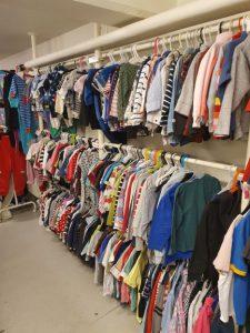 En vägg med barnkläder som hänger på olika ställningar.