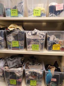 Genomskinliga plastlådor med sorterade småbarnskläder i olika storlekar.