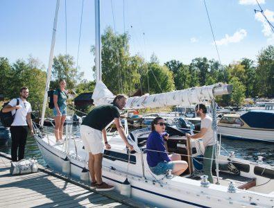Fem personer som gör sig redo för att åka ut med en segelbåt