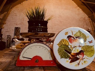 Ett äldre bord i trä med en gammal matvåg på, på vågen står en kruka med blomma i. Bredvid en burk med motiv av en fågel på.