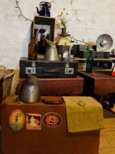 Diverse äldre prylar. Bland annat två äldre resväskor. En gammal kaffekanna i blått. Gamla flaskor i brunt och grönt.