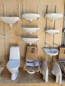 En vägg med flera handfat och på golvet står flera toaletter som är till försäljning hos Sola Byggåterbruk.