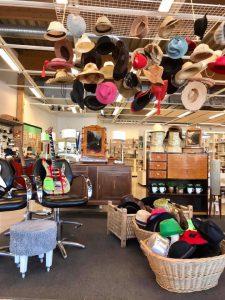 Hattar som hänger från taket, korgar fulla med hattar på golvet under. Kontorsstol med gitarr ståendes i. Byråer i trä i bakgrunden.