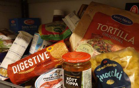 Matvaror i ett skåp som kex, köttsoppa, pasta och tortillabröd.