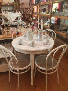 Ett vitt runt bord med fyra stolar står i förgrunden. I bakgrunden syns loppisprylar som porslin och glas med mera på hyllor och bord.