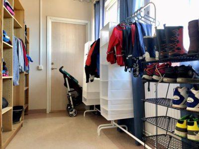 Ett bytesrum med hyllor med kläder, skor och en barnvagn.
