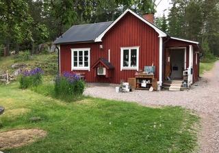 Ett rött torp med gräsmatta framför och en grusväg upp till huset. Framför huset står en träbänk med diverse prylar på.