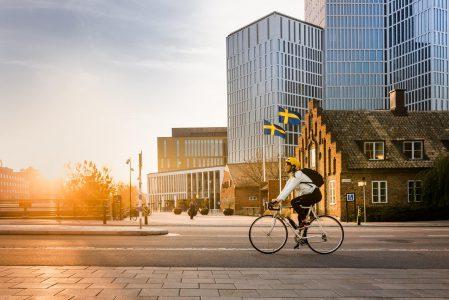 Person cyklar framför Malmö Live, sedd från sidan