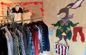 En klädställning med kläder som kan fås. På väggen är en kanin klädd i grön kappa målad.