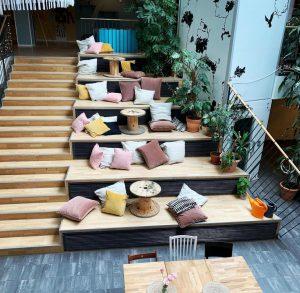 En trappa till vänster och till höger om dem sittplatser i olika nivåer med kuddar i blandade färger.