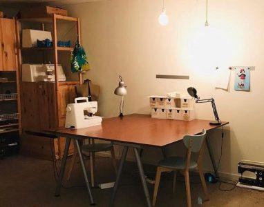 Ett bord med en yta att arbeta på. En skrivmaskin står på bordet. I bakgrunden syns en hylla.
