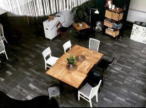 Ett rum tagit uppifrån som visar en öppen yta med ett bord och stolar. Runt om finns ett mindre bord och en hylla samt ett ställe att ladda mobiltelefonen.