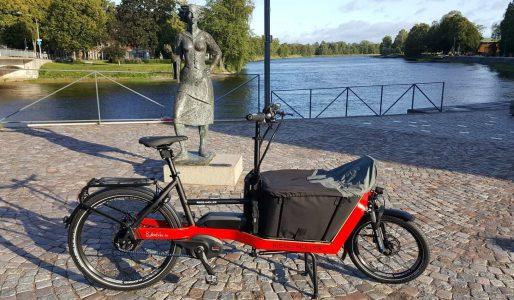 En röd cykel med en mindre lastvagn fram.