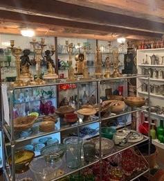 Hyllor fyllda med gamla föremål som vaser, skålar ljusstakar och porslin.