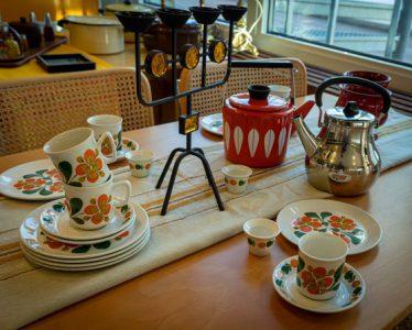 Blommiga koppar, två kaffekannor och en ljusstake på ett bord