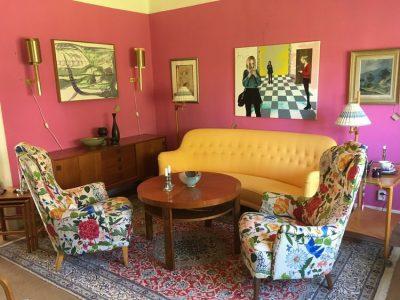 Rum målat i rosa. Två stora tavlor och två mindre på väggarna. En gul soffa och två fåtöljer med blommigt mönster. Antikt soffbord och byrå.