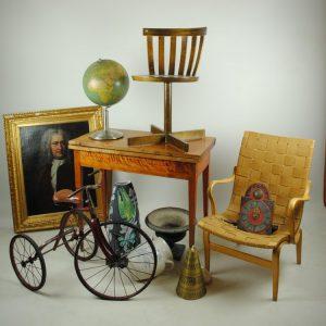 Antikt bord och två antika stolar. En porträttavla, en äldre jordglob och en äldre trehjuling.