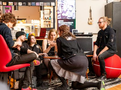 A group of people having a conversation in a room with music instruments