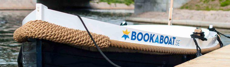 Relingen på en båt i förgrunden, vatten och växtlighet i bakgrunden