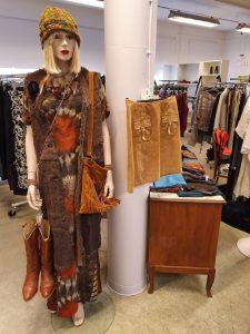 En skyltdocka som är klädd i bruna kläder, mössa och väska. I bakgrunden hänger kläder på klädställningar.