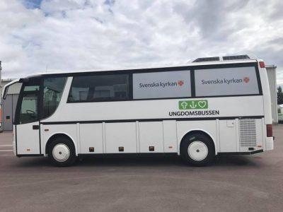 En vit buss. I fönstren syns svenska kyrkans logga. På bussen står det ungdomsbuss.