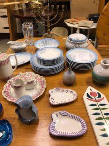 Bord med diverse porslin i rosa och blått på. På bordet finns även tre vaser, en såsnipa, en kandelaber och en kaffekanna.