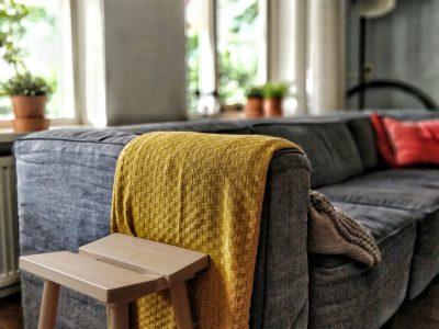 Bild på grå soffa med gul filt, i bakgrunden syns fönster och växter