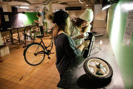 Två personer reparerar en cykel