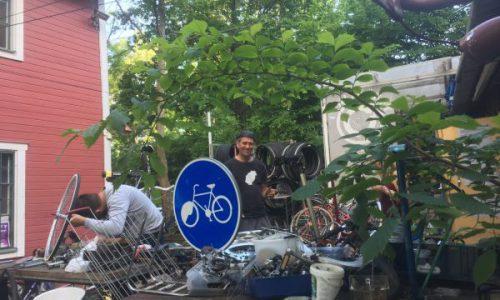 Utomhus, en person rotar bland cyklar, delar och däck