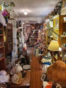 En gång med hyllor längs väggarna fulla i antika prylar till salu. Bland annat lampor, porslin, tavlor med mera.
