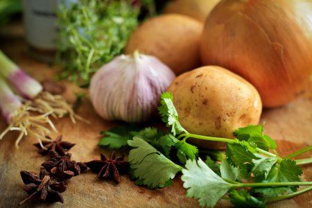 Vitlök, potatis och koriander på ett bord