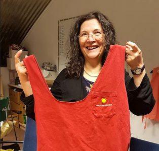 Kvinna som håller upp en egengjord tygkasse i röd färg.