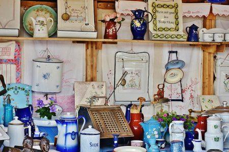 Diverse prylar såsom porslin, tavlor och tyger som ligger på ett bord längs med väggen eller hänger på väggen.