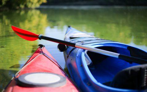 Fören på en röd och en blå kajak. På den blåa kajaken syns även sitsen. Kajakerna ligger i vattnet.