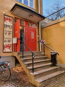 Entre till knastret. En röd dörr på ett gult hus. Stentrappa leder upp till huset.