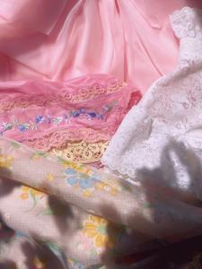 Klädesplagg med spets och brodyr i rosa, vitt och gult.