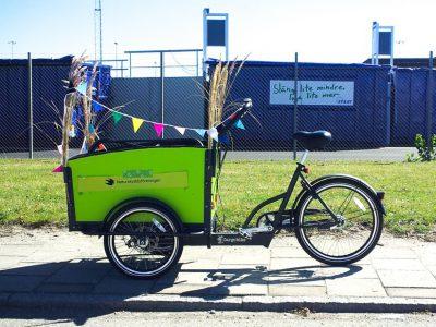 En grön lådcykel som är pyntad med färgglada vimplar, i bakgrunden syns grönt gräs och blåa containrar