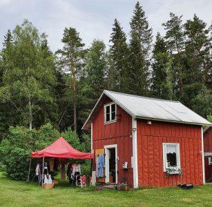 Rött hus med loppistält utanför