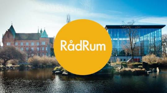 Malmö stadsbibliotek utifrån, med växtlighet i förgrunden, mitt på bilden finns en gul ring som det står RådRum i