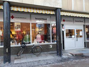 Röda korsets skyltfönster med skyltdockor med olika kläder de har till salu. Framför står en cykel parkerad.