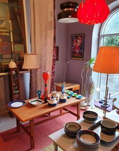 Ett lila rum med en stor tavla på ena väggen och en mindre på den andra. Ett stort fönster till höger om den lilla tavlan. Två retor taklampor. Två retro golvlampor. Två äldre bord som är fyllda med porslin.