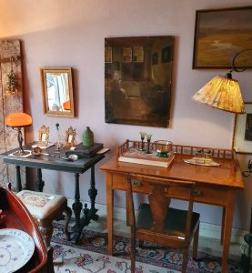 Två antika skrivbord. På dem står en lampa, två ramar, en skål. En äldre golvlampa till häger om ena skrivbordet. Tre olika tavlor på väggarna ovanför. Pall till det vänstra skrivbordet och en stol till de högra. På golvet ligger en äldre matta.