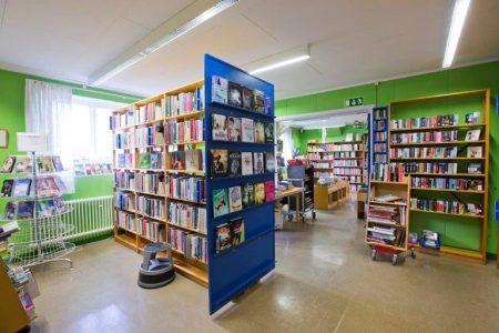 Grönt rum med flera bokhyllor. Mycket böcker i bokhyllorna.